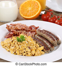 Meal with scrambled eggs, orange, sausages and bacon