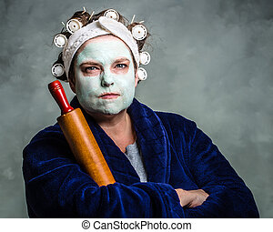 Mean and ugly housewife with facial mask, hair rollers and...