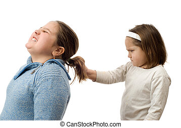 A mean little girl pulling on her older sister's hair, isolated against a white background