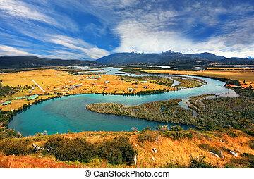 Meandering river bed of yellow autumn coast. Glen Serrano