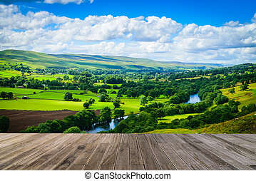 Meandering River making its way through lush green rural farmland in the warm early sunlight with wooden walkway.
