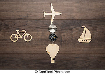 different means of transport made of wood on the table. traveling concept with compass and means of transport as cardinal points