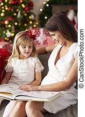 Meantime woman is reading book with girl
