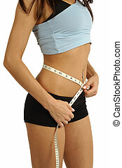 Measure waistline - A tanned slim young woman measuring her...