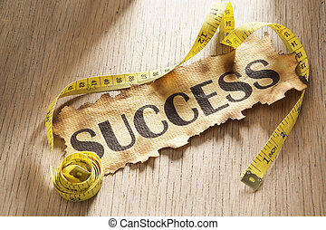 Measurement for success concept by using tape measuring around burnt paper with word success printed on it.
