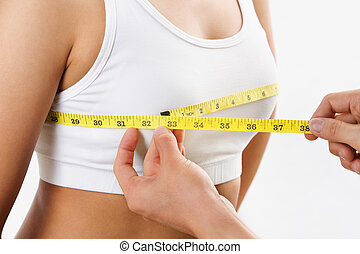 Measuring bra cup size - hand holding yellow measuring tape,...