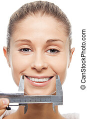 Measuring smile size with trammel - close-up portrait, isolated on white