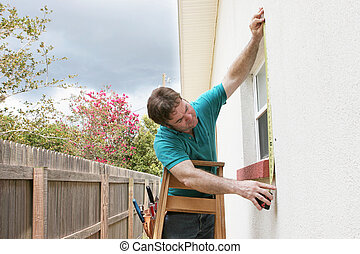 Measuring For Storm Shutters - A carpenter measuring a...
