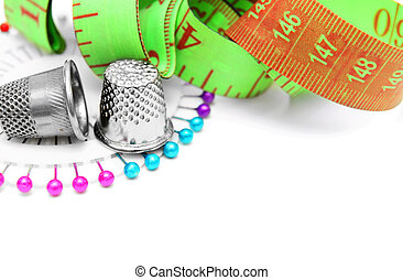Measuring roulette, needles and thimbles. On a white...