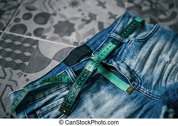 Measuring tape and jeans, weight loss concept