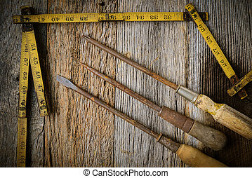 Measuring Tape and Screwdriver on Rustic Old Wood Background