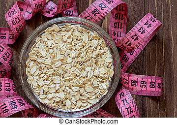 Measuring tape around glass bowl of oats