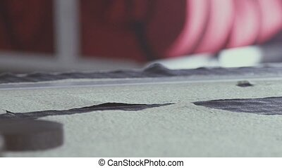 Measuring tape falls on the table and spun. Slow motion.