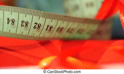 Measuring tape isolated on red cloth, close up - Turquoise...