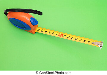 Measuring tape on a green background closeup