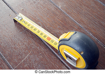 close up of a yellow and back measuring tape on a stained timber deck with the tape measure open to 120 millimetres