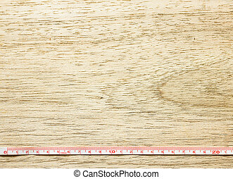 Measuring tape on wooden table texture