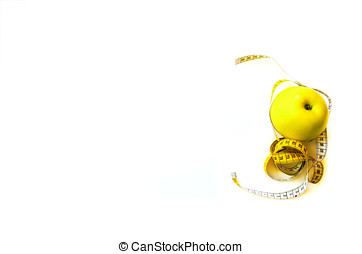 Measuring tape wrapped around fresh tasty yellow apple isolated on white background. Diet, weight loss, fitness, sport concept. Spring and summer fruit. Copy space. Banner.