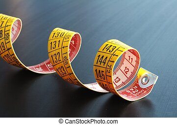 measuring tape - yellow measuring with copyspace on a dark ...