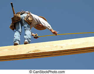 Construction Worker measuring the ceiling support beam in mid-air