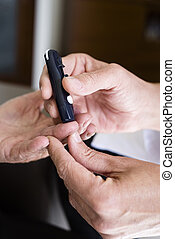 measuring the blood glucose level of an old man - closeup of...