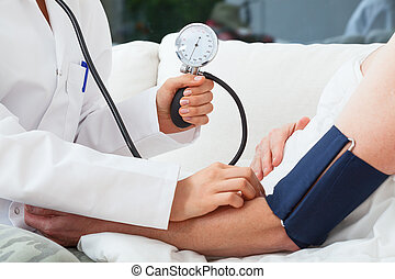 Measuring the blood pressure by doctor with pressure gauge