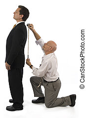 Man getting measured by a tailor on a white background.