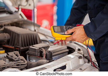 Measuring voltage of a battery - Closeup of a mechanic...