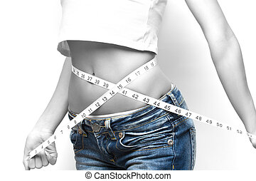 measuring waist - close-up of a woman measuring her waist,...