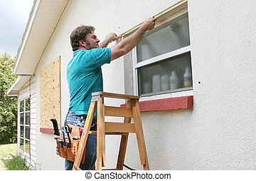 Measuring Windows - A man measuring windows for hurricane...