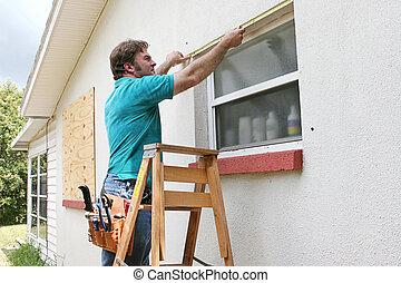 Measuring Windows - A man measuring windows for hurricane...