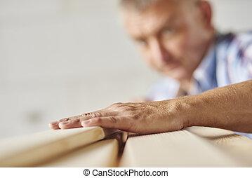 Measuring wooden planks by senior carpenter