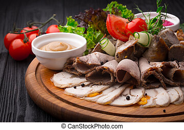 Meat appetizer antipasto on wooden background