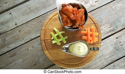 Meat appetizer with sauce. Fried chicken wings in bucket.