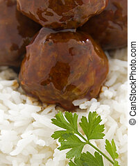 Chinese meat balls in hoisin sauce on a bed of white rice with parsley.