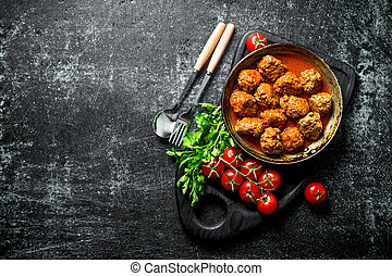 Meat balls in pan on a cutting Board with tomatoes and parsley.