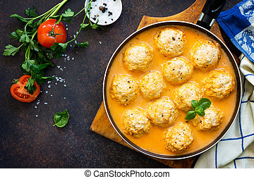 Meat balls turkey in tomato sauce, home cooking on a stone or slate background. Copy space, top view flat lay background.