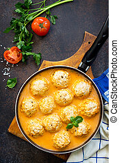 Meat balls turkey in tomato sauce home cooking on a stone or slate background. Top view flat lay background.