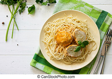 Meat balls turkey with cauliflower in tomato sauce and spaghetti on a wooden table. Copy space, top view flat lay background.