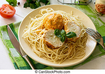 Meat balls turkey with cauliflower in tomato sauce and spaghetti on a wooden table.