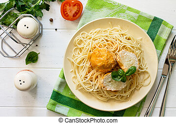 Meat balls turkey with cauliflower in tomato sauce and spaghetti on a wooden table. Top view flat lay background.