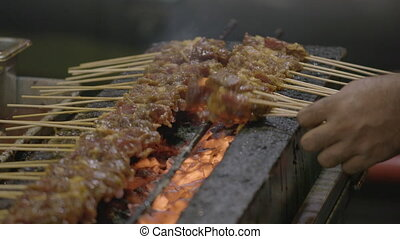 Meat barbecues in bamboo skewers on top of a grill