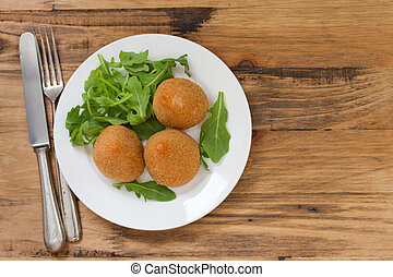 meat croquette on white plate on brown wooden background