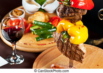 Meat dish - Big tasty roasted meat cuts at skewer on a...
