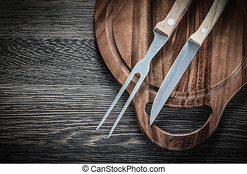 Meat fork knife chopping board on wood background