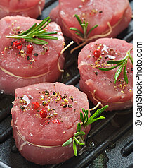 Fresh meat with spices and rosemary on a grill pan.