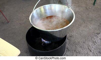 Meat fried in a huge cauldron. 4K.