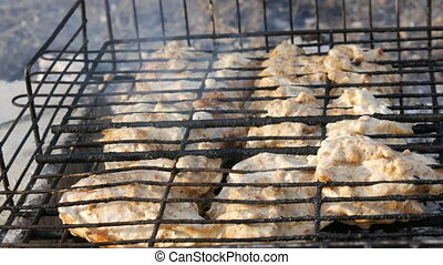 Meat grilling on barbecue grill on nature. Frying Fresh...