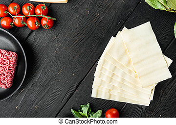 Meat lasagna ingredients, on black wooden table background, top view, flat lay, with copy space for text