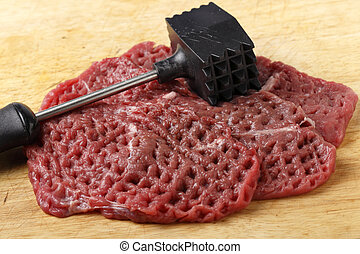 Meat mallet and minute steaks - Three raw minute steaks...